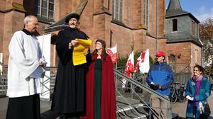 Martin Luther alias Dr. Claus Clausen, evangelischer Stadtpfarrer,  verliest die sieben Thesen für den Freien Sonntag. Neben ihm seine Frau und der Pfarrer der katholischen Heilig-Kreuz-Kirchengemeinde, Monsignore Dr. Michael Kneib.